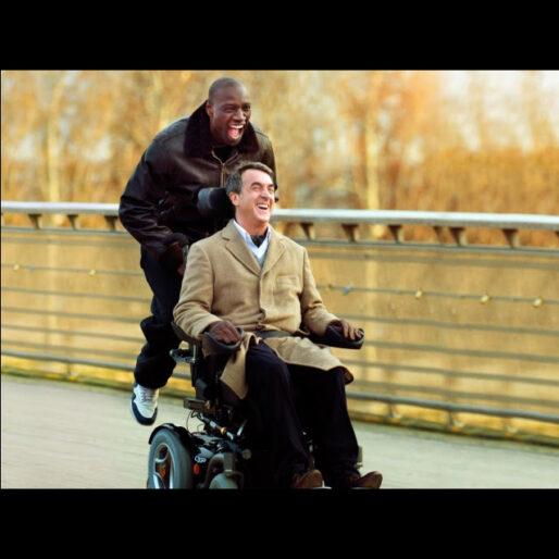 Scena da Quasi Amici: Driss è salito dietro la carrozzina elettrica di Philippe e si fa trasportare; entrambi sorridono divertiti