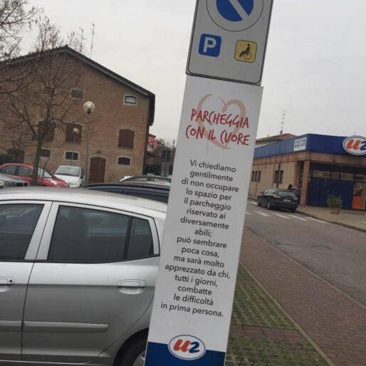 """un parcheggio riservato ai disabili e un cartello che dice: """"Parcheggia con il cuore. Vi chiediamo gentilmente di non occupare lo spazio per il parcheggio riservato ai diversamente abili; può sembrare poca cosa, ma sarà molto apprezzato da chi, tutti i giorni, combatte le difficoltà in prima persona."""""""