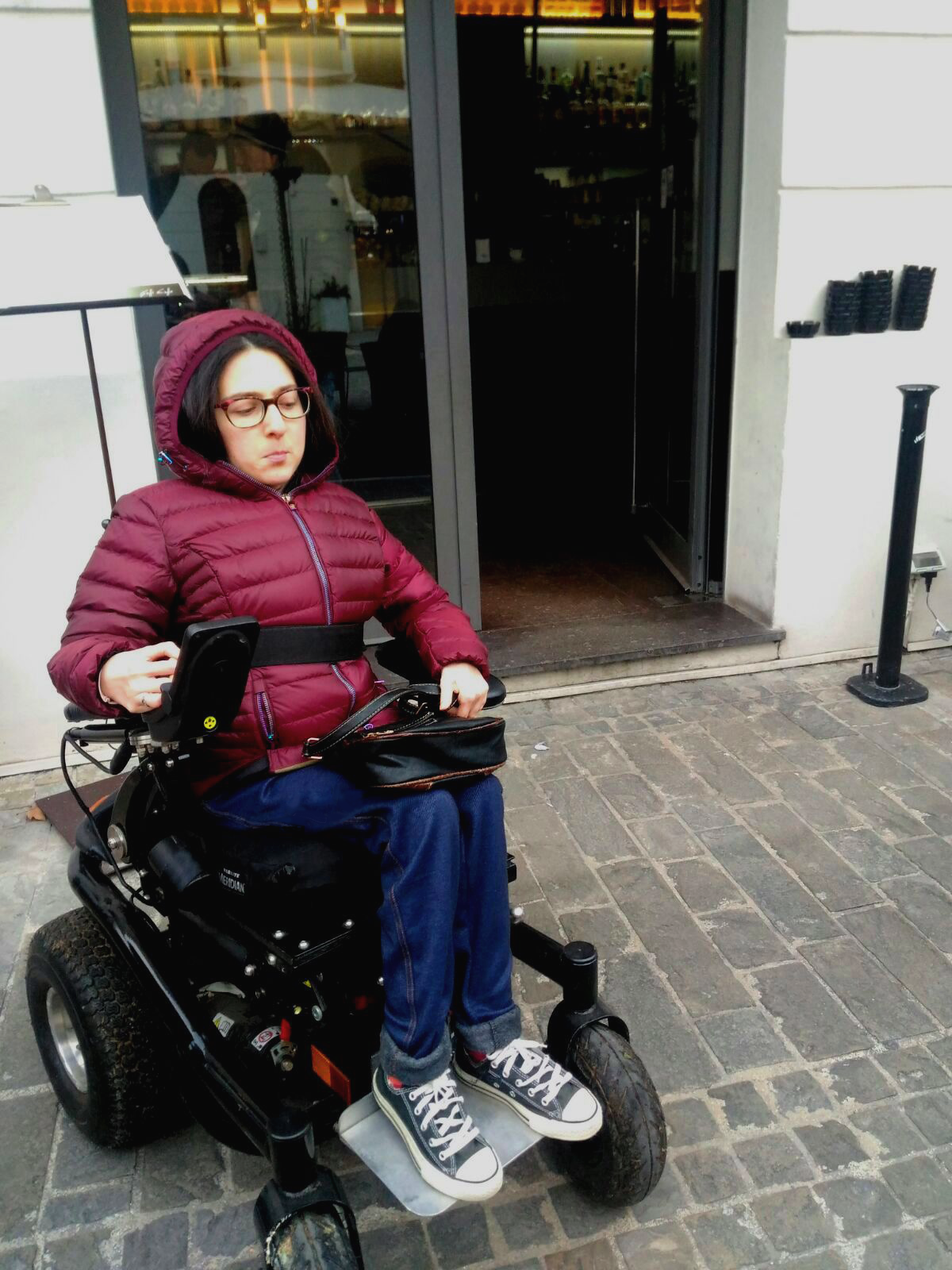 Maria Chiara, seduta sulla sua carrozzina, con espressione scontenta di fronte a un bar di Senigallia con lo scalino senza rampa