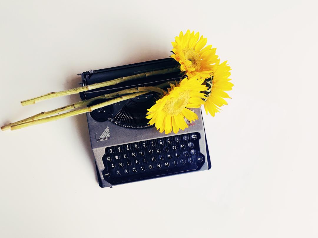 Macchina da scrivere con un fiore giallo in cima