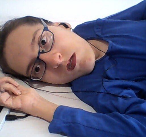 Elena ha i capelli castani raccolti, indossa una maglia blu e gli auricolari. Lo sfondo è bianco.