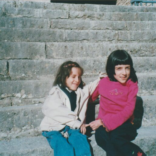 Maria Chiara e Elena hanno sui dieci e sei anni, sono sedute su una gradinata all'aperto e si tengono per mano. Chiara ha un caschetto moro con frangetta tipo Cleopatra, una maglia fucsia e jeans scuri, e Elena i capelli castani con tremila mollettine, un giacchino bianco e jeans blu larghi.