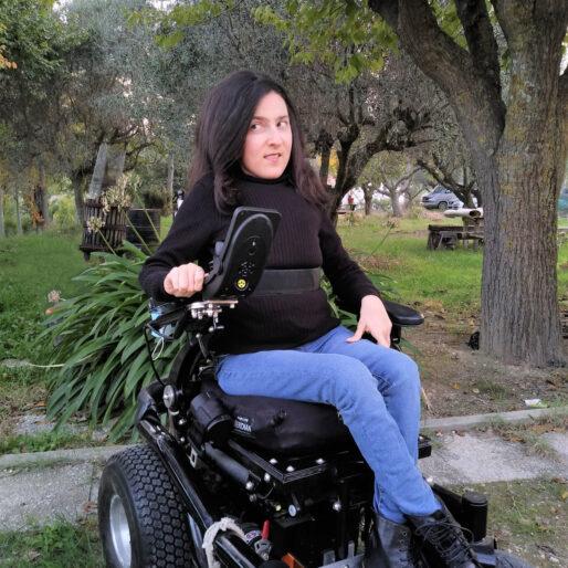 Maria Chiara indossa una maglia nera a collo alto, jeans blu e anfibi neri e guarda di lato. Sullo sfondo, un giardino.