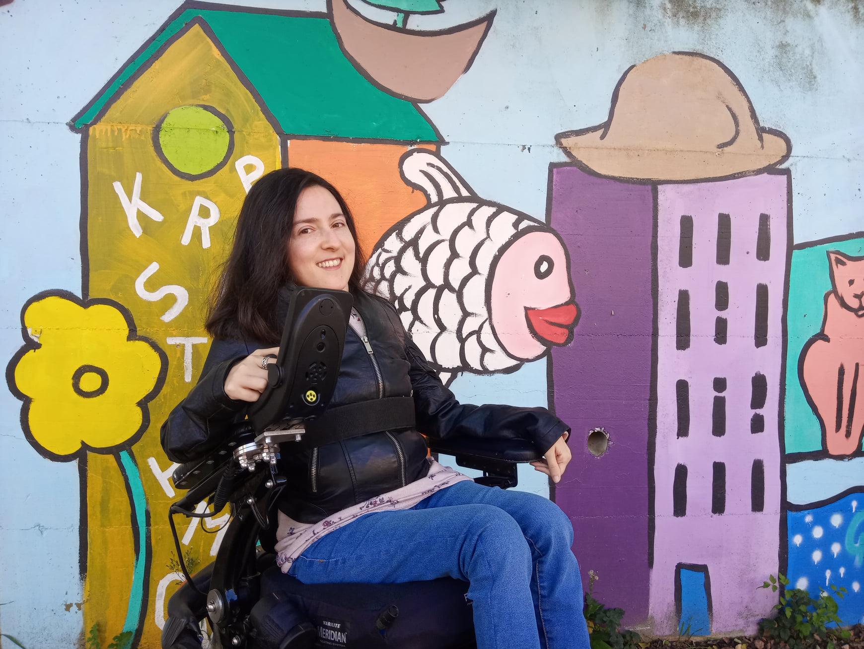 foto di M. Chiara che sorride; è seduta su una carrozzina nera, indossa jeans blu e una giacca nera di pelle, ha i capelli neri. Sullo sfondo, un murale colorato con degli edifici, un fiore, un pesce e un gatto