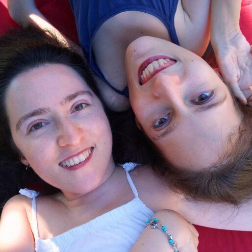 primo piano di M. Chiara e Elena distese su una brandina rossa con le teste vicine ma Elena a testa in giù. M. Chiara ha i capelli neri e indossa una canottiera bianca, Elena ha i capelli castani e una canottiera blu. Entrambe sorridono e M. Chiara tiene la mano di Elena