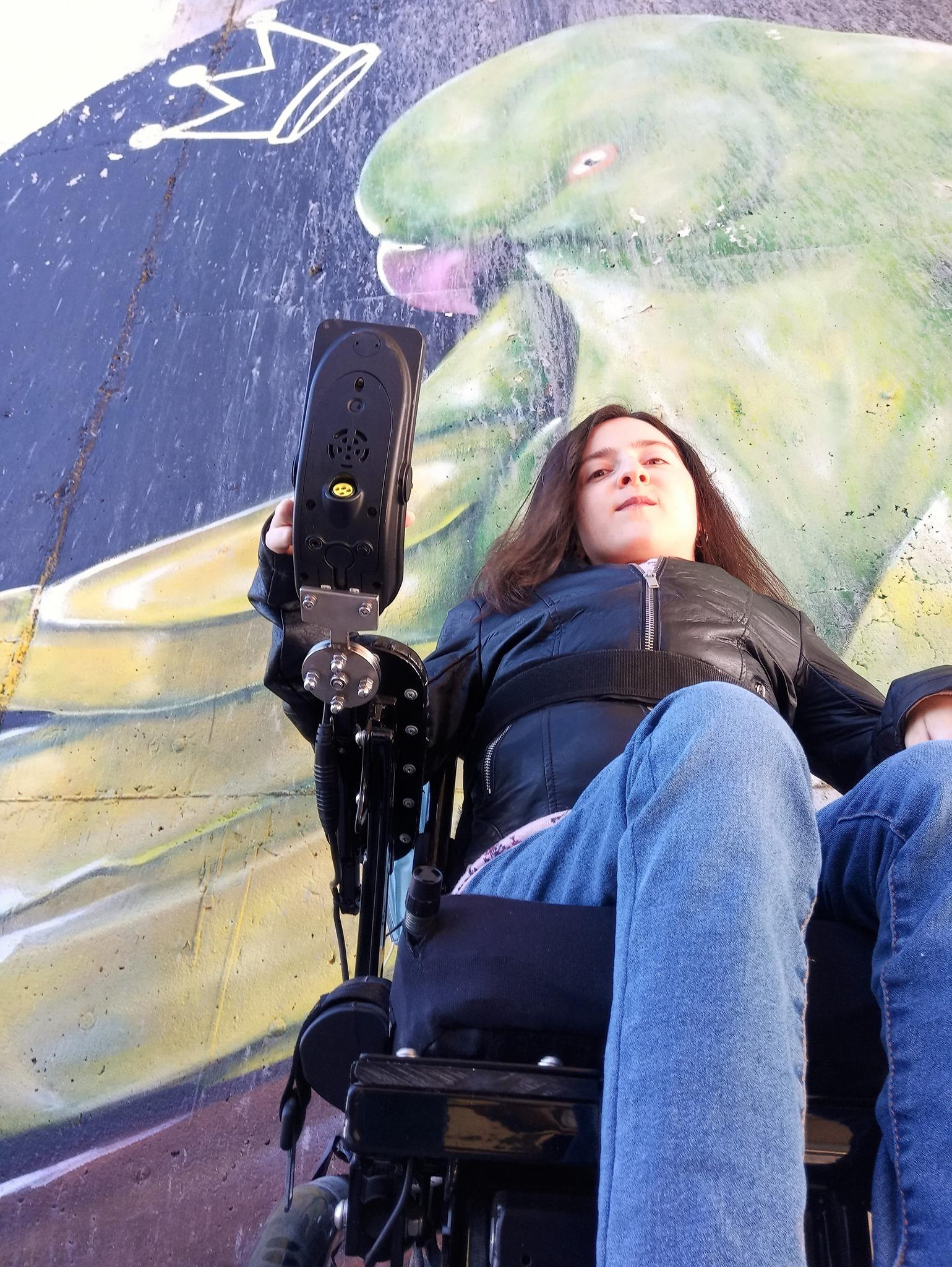 foto di M. Chiara inquadrata dal basso; è seduta su una carrozzina nera, indossa jeans blu e una giacca nera di pelle, ha i capelli neri. Sullo sfondo, un murale con un pappagallo