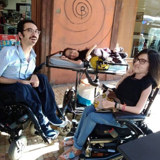 Elena e Francesco* sotto dei portici in una giornata di sole. Usano tutti e tre la carrozzina elettrica.