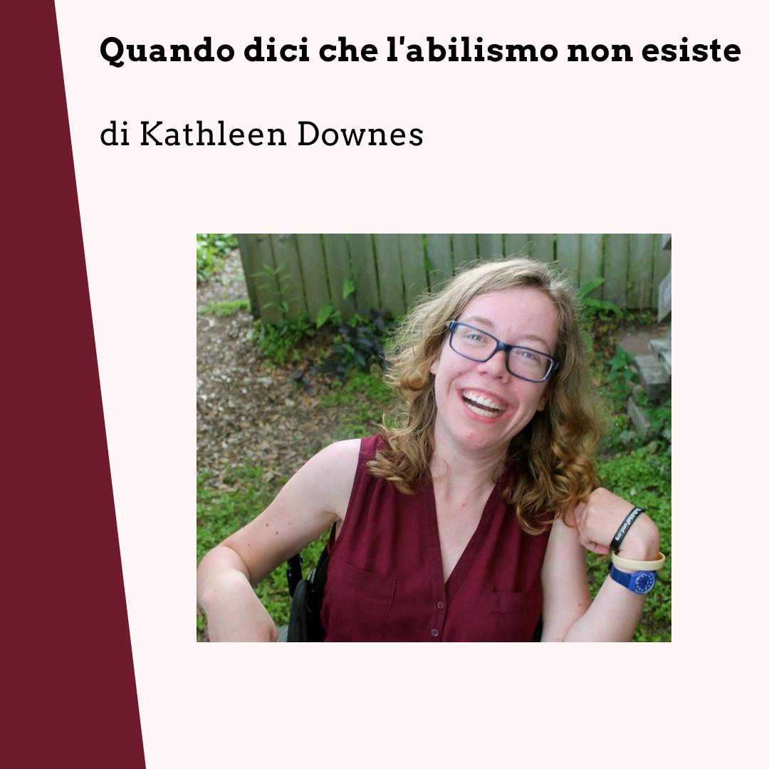 Kathleen Downes è seduta in una carrozzina. Ha i capelli biondi ondulati e gli occhiali, sta sorridendo e indossa un vestito bordeaux. Sullo sfondo, un giardino