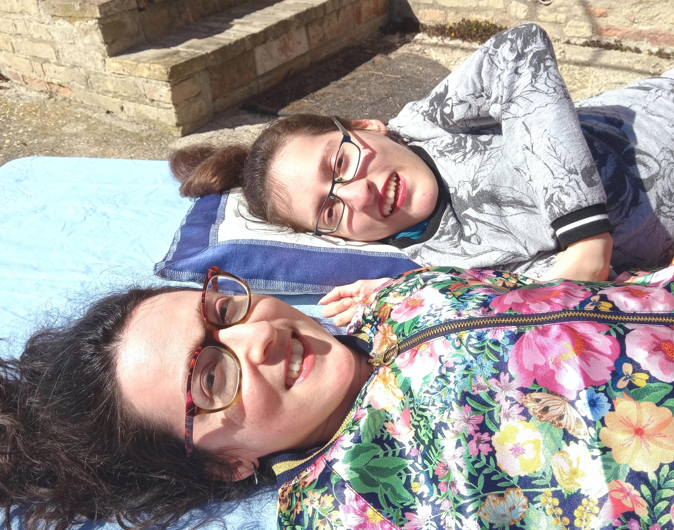 Elena e M. Chiara sono sdraiate su una brandina davanti a casa e sorridono nonostante un sole impietoso negli occhi. Elena ha una felpa a motivi floreali grigia e M. Chiara una felpa lucida colorata.