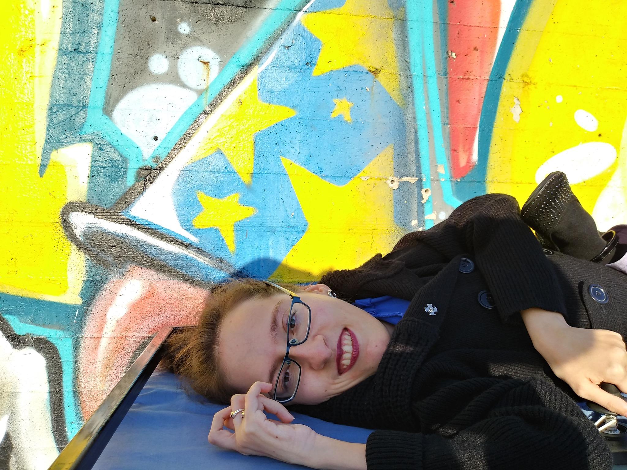 foto di Elena che sorride; indossa una giacca nera con dei grossi bottoni e ha i capelli castani legati in una coda. Sullo sfondo, dei graffiti colorati.