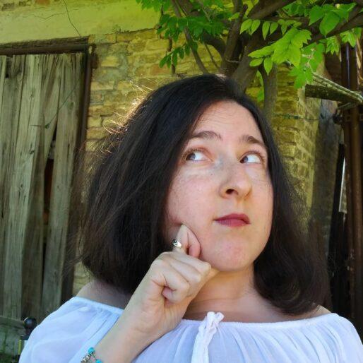 primo piano di Chiara con un'espressione pensierosa. Indossa una maglia bianca e ha capelli neri fino alle spalle. Sullo sfondo, un albero e una vecchia porta di legno